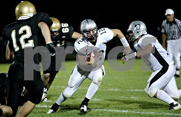 Rob Winner –  rwinner@daily-chronicle.com<br /> Kaneland quarterback Joe Camiliere carries the ball during the first half of Friday night's game in Sycamore.<br /> 09/18/2009