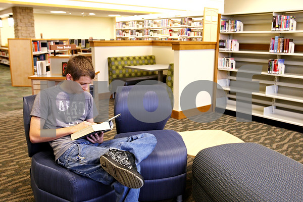 """Beck Diefenbach  -  bdiefenbach@daily-chronicle.com<br /> <br /> Josh Lockard, of Somonauk reads """"Brisingr,"""" at the Teen Zone of the new Somonauk Public Library in Somonauk, Ill., on Thursday Aug. 27, 2009."""