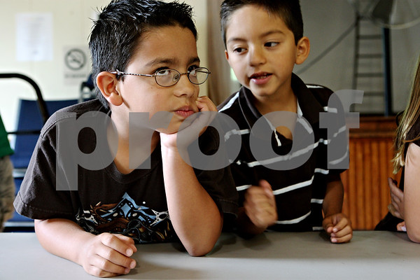 Rob Winner – rwinner@daily-chronicle.com<br /> Adrian Godnez (left), 7, and Landon Garcia, 7, ponder a question about managing money during Wednesday's summer program class at Conexión Comunidad in DeKalb.<br /> 07/22/2009