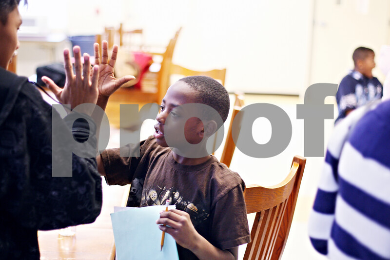 Beck Diefenbach  -  bdiefenbach@daily-chronicle.com<br /> <br /> Center, Brandon Pitts, 7, gives a high-five to Rother Delos Santos, 17, of the Philippine Youth Leadership Program, after he helped Pitts with his homework at Hope Haven in DeKalb, Ill., on Monday April 13, 2009.