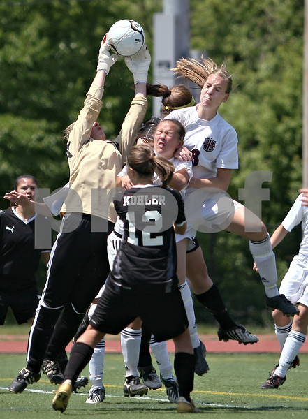 Beck Diefenbach  -  bdiefenbach@daily-chronicle.com<br /> <br /> Sycamore goal keeper Sarah Fischer (left) catches a corner kick before Wheaton Academy's Meghan Grant (top right) can get her head on it during the second half of the Class 2A state semifinal game at North Central College in Naperville, Ill., on Friday June 5, 2009. Sycamore lost to Wheaton Academy 5-2 and will face Chatham Glenwood for third place on Saturday.
