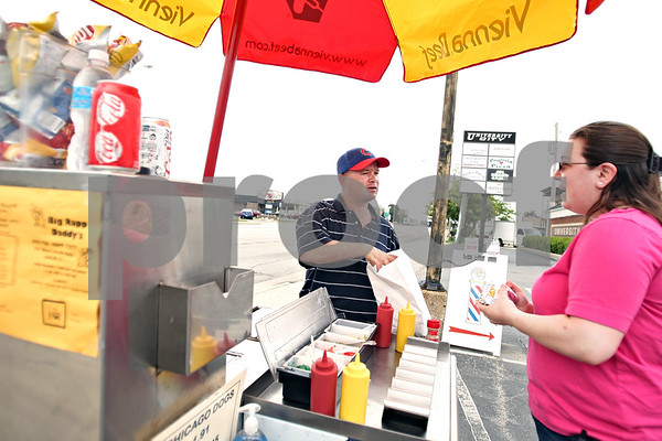 Beck Diefenbach  -  bdiefenbach@daily-chronicle.com<br /> <br /> David Rapp serves three Chicago style hot dogs to Myra Walls, of Malta, at David's Big Rapp Daddy hot dog stand on Lincoln Highway in DeKalb, Ill., on Tuesday May 26, 2009.