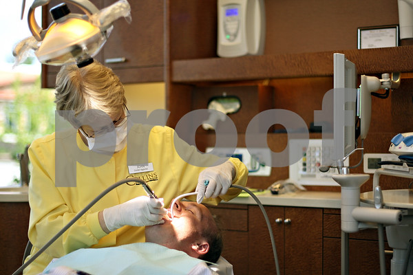 "Beck Diefenbach  -  bdiefenbach@daily-chronicle.com<br /> <br /> Dental hygienist Joan Kaul cleans the teeth of Clay Campbell, of Sycamore, during a visit to Collins Dental Group in Sycamore, Ill., on Thursday June 11, 2009. ""I probably grind (my teeth),"" Campbell said. ""But I just try to get here ever six months."""