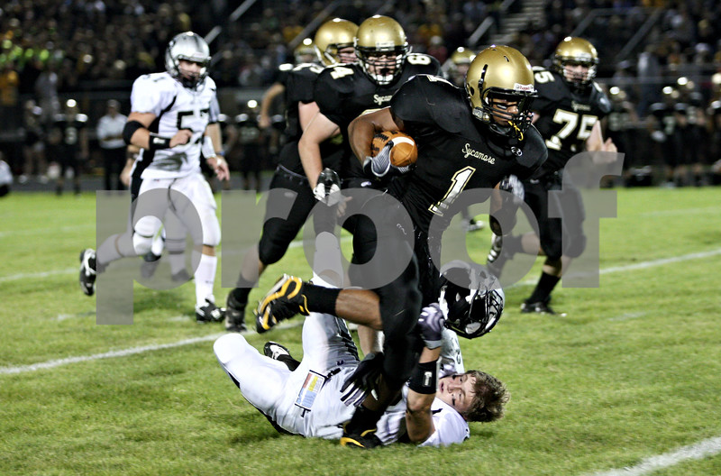 Rob Winner –  rwinner@daily-chronicle.com<br /> Even after losing his helmet, Kaneland's Blake Serpa (bottom) is able to trip up Sycamore's Marckie Hayes during a run in the first quarter of Friday night's game in Sycamore.<br /> 09/18/2009