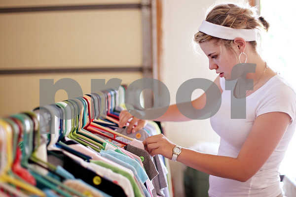 Beck Diefenbach  -  bdiefenbach@daily-chronicle.com<br /> <br /> Renee Larson, of DeKalb, goes through her neighbor's garage sale clothing rack in DeKalb, Ill., on Thursday June 18, 2009.