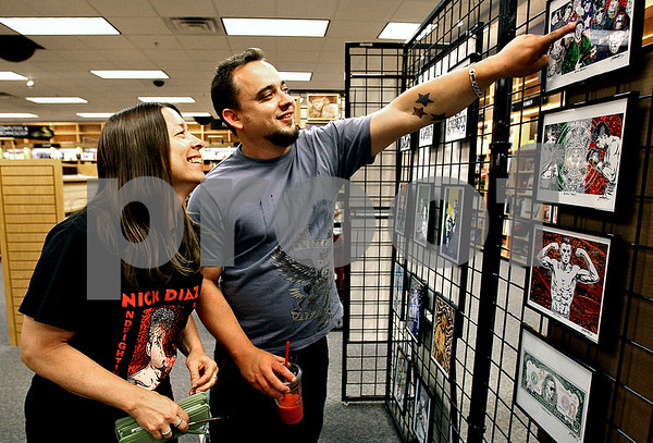 Rob Winner – rwinner@daily-chronicle.com<br /> Dawn McAllister (left), mother of artist Justin McAllister, looks at her son's art during the Borders Nite Out event in July.<br /> 07/11/2009