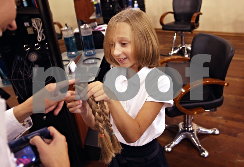 Beck Diefenbach  -  bdiefenbach@daily-chronicle.com<br /> <br /> Emily Morfoot, 8, inspects her former locks after getting her hair cut at Dolce Vita Salon and Day Spa in Sycamore, Ill., on Tuesday Oct. 6, 2009. This is the second time Emily is donating her hair to Locks of Love.