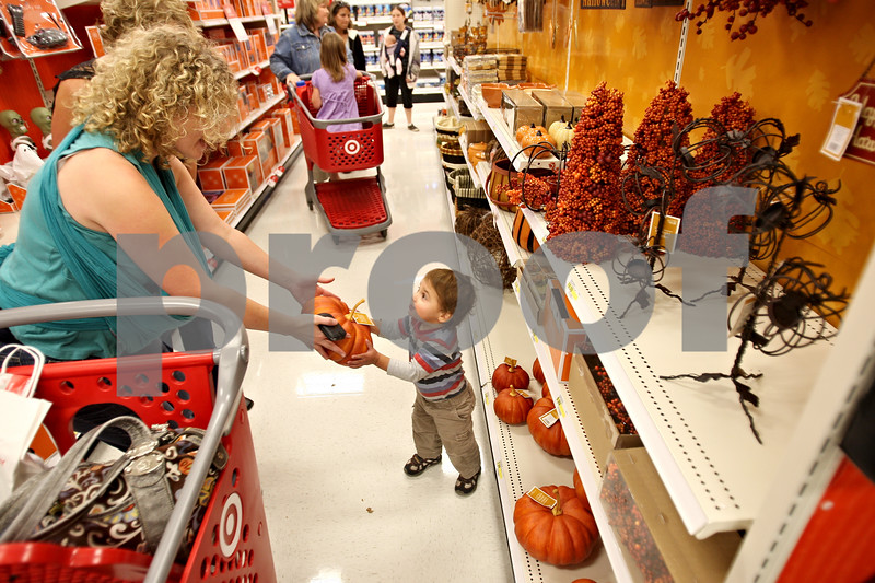 """Beck Diefenbach  -  bdiefenbach@daily-chronicle.com<br /> <br /> Charlie Sanderson-Haque, 1, hands a fake pumpkin to his mother Jill, while shopping in the rebuilt Target Store in DeKalb, Ill., on Tuesday Oct. 6, 2009. 'We've been going through withdrawal,"""" Jill said."""