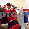 Beck Diefenbach  -  bdiefenbach@daily-chronicle.com<br /> <br /> Nayeli Hildago, left, fixes the collar of Javier Valencia, an employee for Going Postal, as he dons the rest of the costume as the new company's mascot before he distributes fliers in Sycamore, Ill., on Wednesday March 18, 2009.