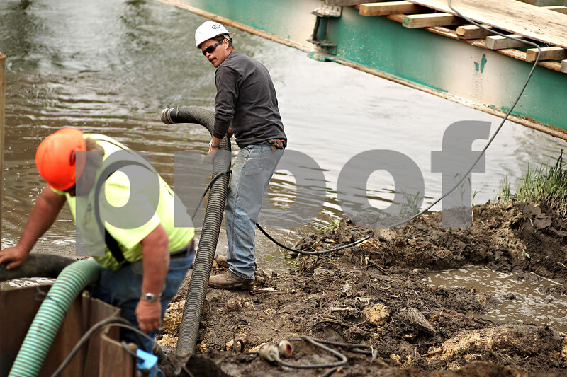 Beck Diefenbach  -  bdiefenbach@daily-chronicle.com<br /> <br /> Civil Construction's Mike Brown, top, places a drain pipe during construction of a bridge over the Kishwuakee River north of Sycamore, Ill., on Tuesday May 5, 2009.