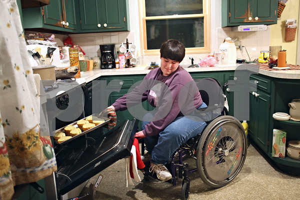 "Beck Diefenbach – bdiefenbach@daily-chronicle.com<br /> <br /> Emily Lampkin, 20, of Sycamore, leans away from the onslaught of heat as she pulls a tray of garlic bread from the oven as she prepares dinner for her family at her home in Sycamore, Ill., on Thursday Feb. 19, 2009. ""I just started putting things in the oven,"" Emily said. Emily, who lives with Spina Bifida and Shunted Hydrocephalus, practices at home what she has learned at Life School."