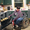 """Beck Diefenbach – bdiefenbach@daily-chronicle.com<br /> <br /> Emily Lampkin, 20, of Sycamore, leans away from the onslaught of heat as she pulls a tray of garlic bread from the oven as she prepares dinner for her family at her home in Sycamore, Ill., on Thursday Feb. 19, 2009. """"I just started putting things in the oven,"""" Emily said. Emily, who lives with Spina Bifida and Shunted Hydrocephalus, practices at home what she has learned at Life School."""