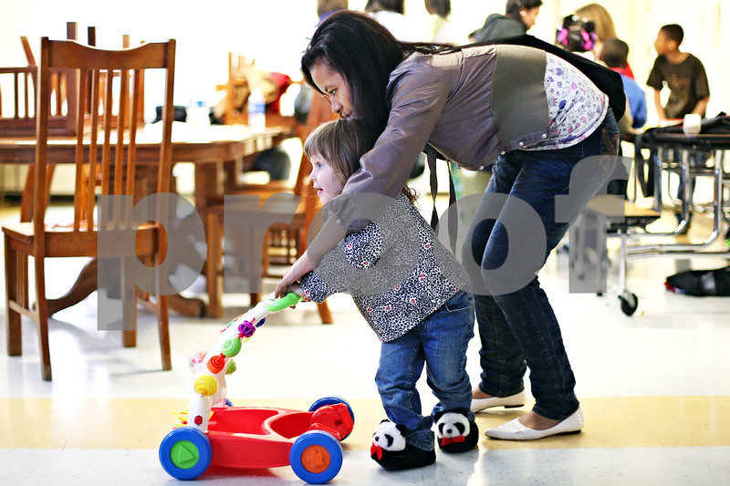 Beck Diefenbach  -  bdiefenbach@daily-chronicle.com<br /> <br /> Beth Cilipiha, 3, gets some help with her cart from Fatimah Ditti, 16, of the Philippine Youth Leadership Program at Hope Haven in DeKalb, Ill., on Monday April 13, 2009.