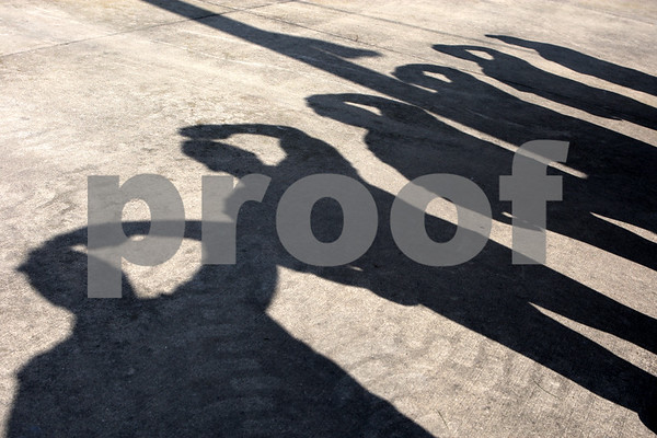 Rob Winner rwinner@daily-chronicle.com<br /> On Friday at the Sandwich Fair, shadows of Sandwich Firefighters standing at attention cover the ground near the Ag Land Stage during a ceremony to remember September 11, 2001.<br /> 09/11/2009