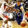 Beck Diefenbach  -  bdiefenbach@daily-chronicle.com<br /> <br /> Geneva's Will Doeckel (23, right) dribbles past Rockford Jefferson's Javon Henderson (21) during the first quarter of the game at DeKalb High School in DeKalb, Ill. on Wednesday Dec. 23, 2009.