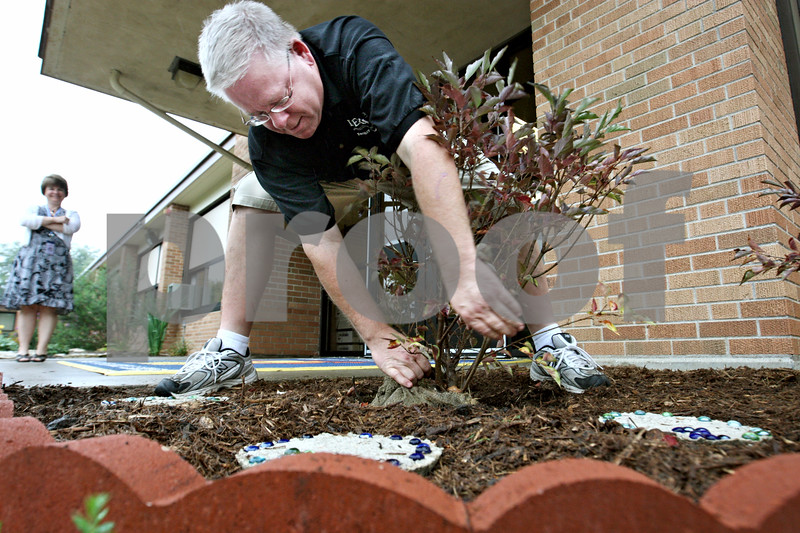 """Rob Winner –  rwinner@daily-chronicle.com<br /> Principal Cristy Meyer watches as head custodian Bruce plants the last of three lilac plants in front of Lincoln Elementary School in DeKalb on Tuesday morning. The lilac garden was planted in honor and memory of Christina Setchell, a dedicated parent and friend of the school. """"Chris will be very much missed by the Lincoln community,"""" said principal Cristy Meyer on Tuesday.<br /> 09/19/2009"""