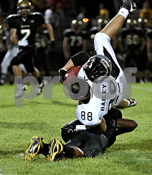 Rob Winner –  rwinner@daily-chronicle.com<br /> Kaneland's Ryley Bailey loses his helmet after a hit from Sycamore's Marckie Hayes in the first quarter.<br /> 09/18/2009