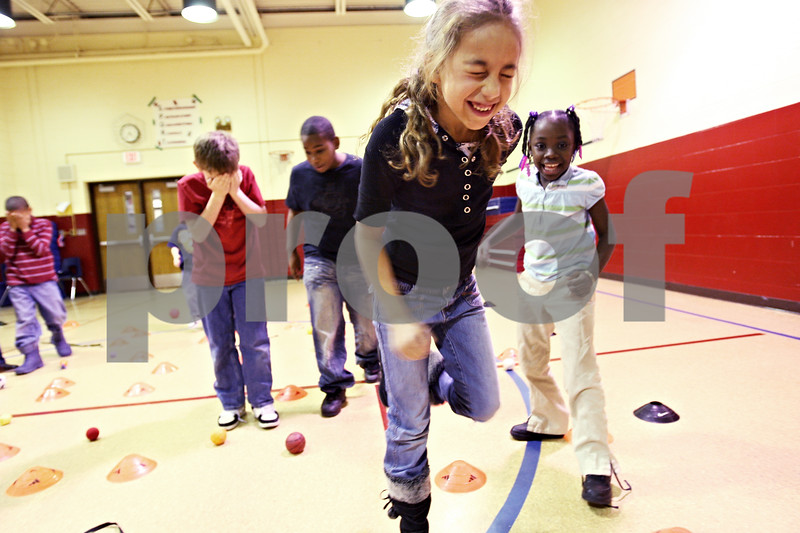 Beck Diefenbach  -  bdiefenbach@daily-chronicle.com<br /> <br /> Second grader Elaina Mitchell, center, leaps through an obstacle course during an after school program run in conjunction with the YMCA at Little John Elementary School on Tuesday Dec. 15, 2009.