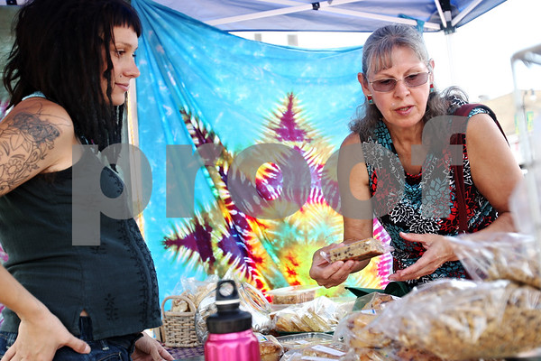 Beck Diefenbach  -  bdiefenbach@daily-chronicle.com<br /> <br /> Right, Jeannette Vaupel, of Genoa, looks though organic goods from Hillary Stanley, left, of Sunny Day Bakery, at the farmers market in downtown DeKalb, Ill., on Thursday July 9, 2009.