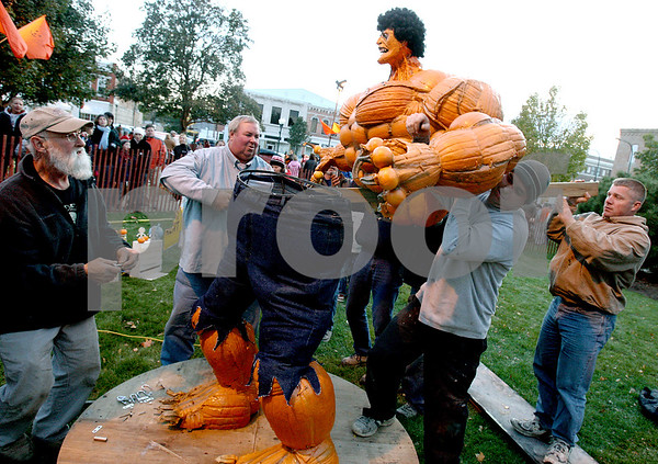 "ROB WINNER | Chronicle News Group<br /> Lynden Bute (left), of Sycamore, watches as friends of his help lift the top half of his Pumpkin Fest creation named ""The Incredible Pumk."" Wednesday was the first day of the 47th annual Pumpkin Festival which runs through Sunday at the DeKalb County Courthouse lawn in Sycamore."