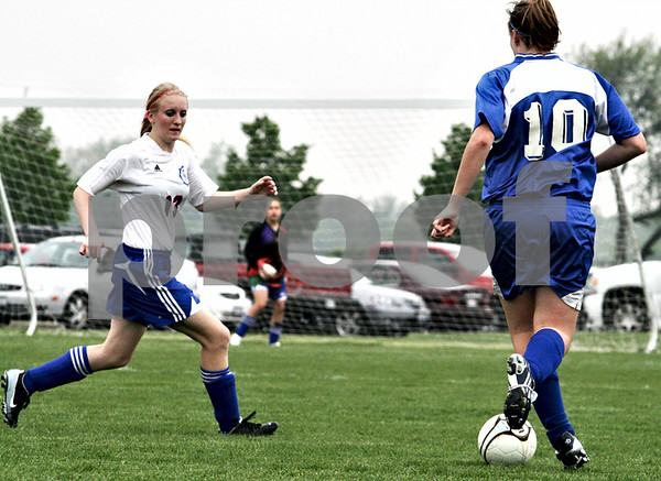 Randi Stella – rstella@daily-chronicle.com<br /> <br /> Genoa's Katrine Capek (13) runs to intercept Westminster's Rachel Doby (10) at the regional quarter final at Genoa-Kingson High School in Genoa, Ill., on Wednesday May 13th, 2009.