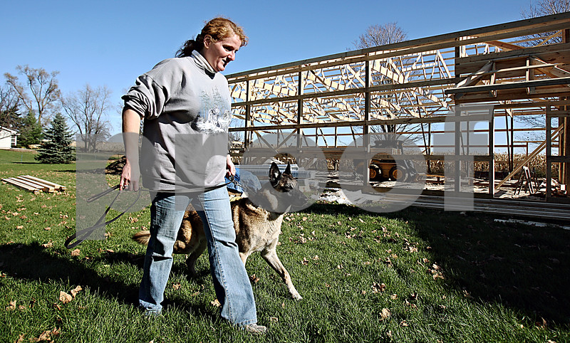 Rob Winner – rwinner@daily-chronicle.com<br /> Kim Bobka takes her dog Lightning for a walk outside of her home where she runs her business Teacher's Pet K-9 School in Sycamore. Bobka is in the process of having a new facility built on the property to accommodate the expansion of her business.<br /> 11/05/2009