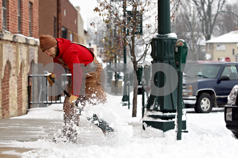 Rob Winner – rwinner@daily-chronicle.com<br /> Joe Larsen removes snow from a sidewalk wit a shovel in downtown Sycamore on Tuesday morning.<br /> 12/08/2009