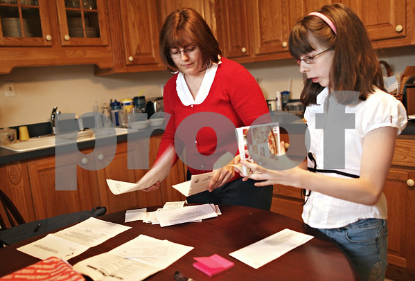 Beck Diefenbach  -  bdiefenbach@daily-chronicle.com<br /> <br /> Tracy Busby, center, and her daughter Jennifer, 13, go through their daily mail and coupons at home in DeKalb, Ill., on Friday May 15, 2009.