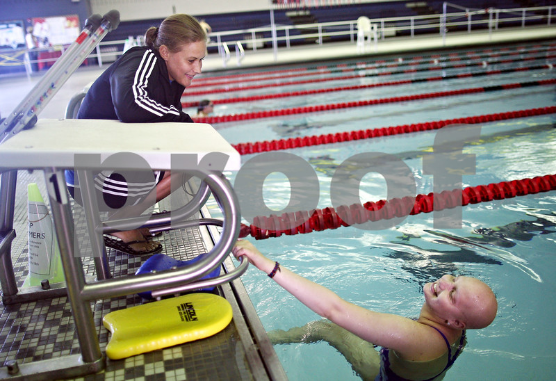 Beck Diefenbach  -  bdiefenbach@daily-chronicle.com<br /> <br /> Grace Waller, right, shares a laugh with her coach Leah Eames between laps during a swimming practice at the Kishwuakee YMCA in Sycamore, on Wednesday July 15, 2009.