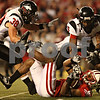 Beck Diefenbach – bdiefenbach@daily-chronicle.com<br /> <br /> Northern Illinois' Mike Sobol (38) and Chris Smith (5) take down Wisconsin's Maurice Moore (23) during the third quarter of the game in Madison, Wisc., on Saturday Sept. 5, 2009. Wisconsin beat Northern Illinois 28 to 20.