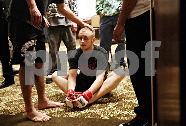 Beck Diefenbach  -  bdiefenbach@daily-chronicle.com<br /> <br /> Steven Kick, 18, of Sandwich, Ill., receives a pat on the head has he stretches before his match in Power Fights 14, an amateur cage-fighting mixed-martial arts event at the Timber Creek Inn and Suites, in Sandwich, on Saturday Oct. 21, 2009.