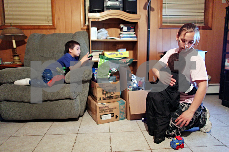 Beck Diefenbach  -  bdiefenbach@daily-chronicle.com<br /> <br /> Mindy Albright, far right, hugs her youngest son Dominic, 1, as her other son, Evan McCormick, 5, watches television at their new apartment in DeKalb, Ill., on Saturday May 2, 2009. Mindy works two jobs, to support her two sons.