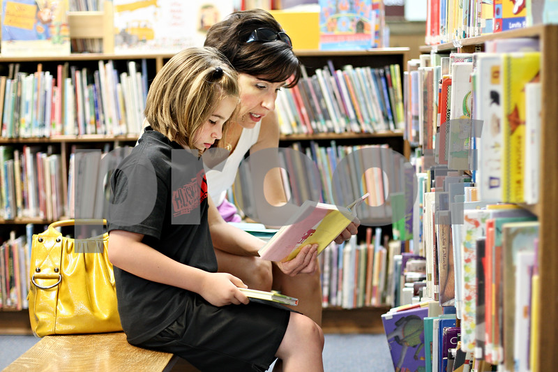 """Beck Diefenbach  -  bdiefenbach@daily-chronicle.com<br /> <br /> Patricia Klonoski, of DeKalb, previews a book with her daughter Olivia, 8, at the DeKalb Public Library on Monday June 15, 2009. """"Stocking up on summer reading,"""" Klonoski said."""