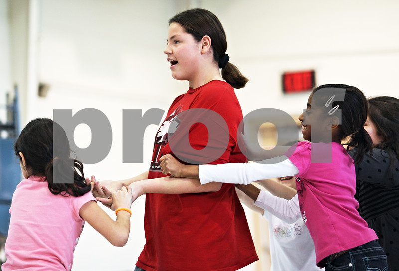 Beck Diefenbach  -  bdiefenbach@daily-chronicle.com<br /> <br /> Malta fourth grader Brianne Anderson, right, helps move fifth grader Cory Mata, center, to the front of the class to help lead them during their dance rehearsal after school in Malta, Ill., on Wednesday Jan 21, 2009.