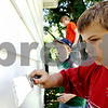Rob Winner – rwinner@daily-chronicle.com<br /> Noah Hansen (front to back), 8, concentrates as he and his brothers, Jacob, 10, and Ethan, 12, help paint the home of Lucille Harold in DeKalb on Saturday afternoon. The brothers along with a group of Salvation Army volunteers helped paint the home.<br /> 07/11/2009