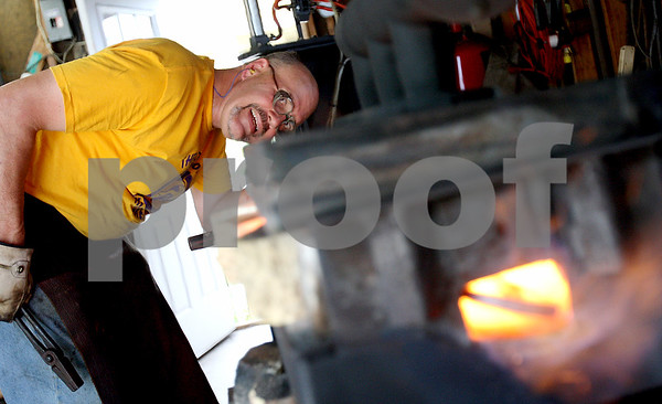 Rob Winner – rwinner@daily-chronicle.com<br /> While working in his garage on Tuesday afternoon, Chris Hubbard looks into his forge as a piece of steel begins to glow orange. Pieces of Hubbard's work can be purchased at the Ellwood House and Museum art show this Sunday.<br /> 06/30/2009