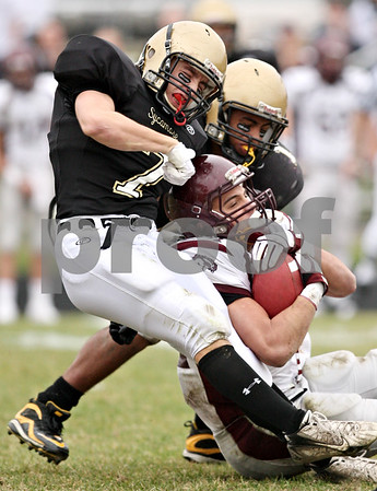 Beck Diefenbach  -  bdiefenbach@daily-chronicle.com<br /> <br /> Sycamore defensive backs Danny Schroeder (7, left) and Marckie Hayes (1, right) struggle to take down Montini running back Nick Campanella (24) during the third quarter of the playoff game at Sycamore High School in Sycamore, Ill., on Saturday Nov. 14, 2009.