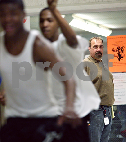 Beck Diefenbach – bdiefenbach@daily-chronicle.com<br /> <br /> DeKalb High School boys track coach Tim Holt watches as two of his relay runners rehearse baton hand-offs during practice at DeKalb High School in DeKalb, Ill., on Tuesday March 10, 2009.