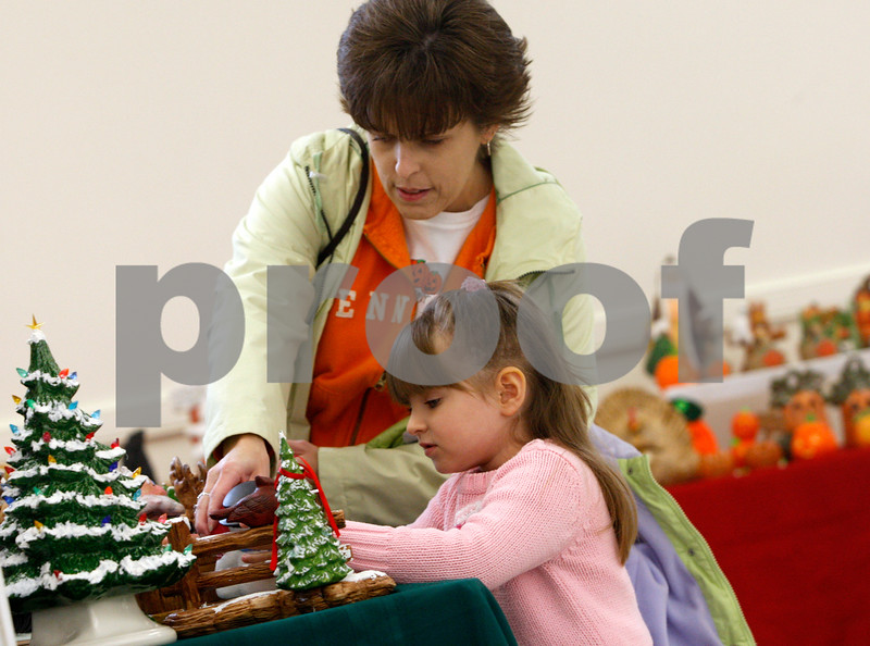 ROB WINNER | rwinner@daily-chronicle.com<br /> Debbie Hennessee, of Cortland, and her 3-year-old daughter, Taylor, browse the crafts at St. Mary's Memorial Hall in Sycamore on Friday afternoon. The St. Mary's Craft Show will continue today, Saturday, from 9 a.m. to 5 p.m.<br /> 10/24/2008