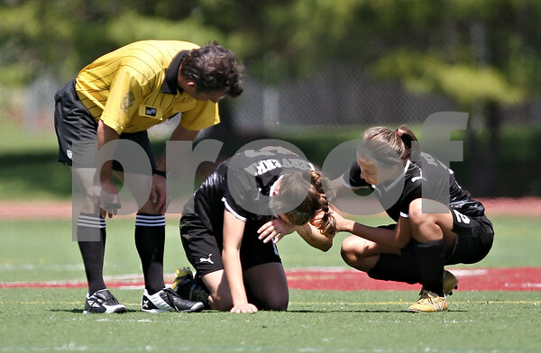 Beck Diefenbach  -  bdiefenbach@daily-chronicle.com<br /> <br /> Sycamore's Sarah Cervenka (center) is tended to by Mary Kohler (right) after she hit her heard on the ground during the first half of the Class 2A state semifinal game against Wheaton Academy at North Central College in Naperville, Ill., on Friday June 5, 2009.