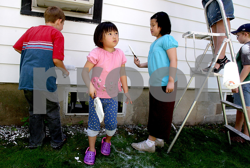 Rob Winner – rwinner@daily-chronicle.com<br /> On Saturday afternoon, Grace Cho, 6, stops painting for a moment to get more paint as she, her family and other volunteers from the Salvation Army helped paint the home of Lucille Harold in DeKalb.<br /> 07/11/2009