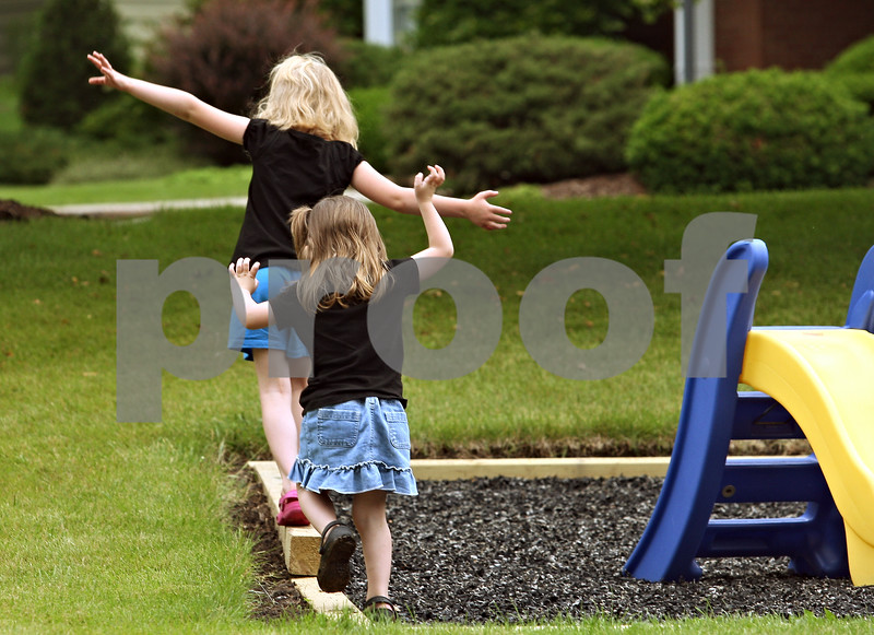 Beck Diefenbach – bdiefenbach@daily-chronicle.com<br /> <br /> Front, Scharlotte Wig (CQ), 3, follows her sister Rylynne's (CQ) balancing act between rain storms at their Sycamore home on Friday June 19, 2009.