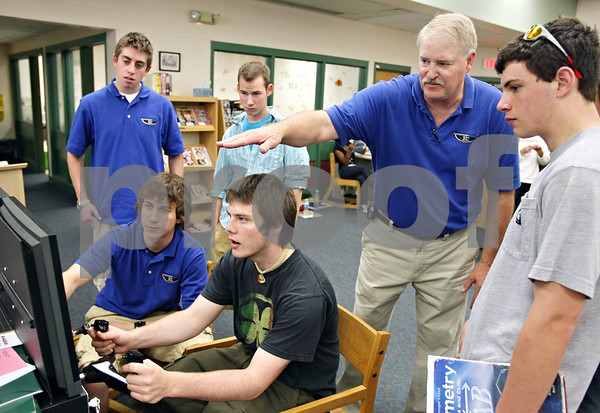 Beck Diefenbach  -  bdiefenbach@daily-chronicle.com<br /> <br /> (Second from right) Steve Durin, of Kishwuakee College, explains the flight simulator as Sycamore senior James Ahern flies a Cessna 182 as part of career day at Sycamore High School in Sycamore, Ill., on Thursday May 7, 2009.