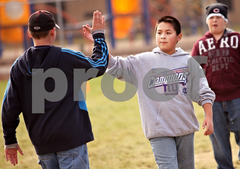 Beck Diefenbach  -  bdiefenbach@daily-chronicle.com<br /> <br /> Fifth grader Enrique Flores gives a high five after his team scored a goal as part of a micro soccer tournament during physical education class at Hiawatha Elementary School on Wednesday Nov. 4, 2009.
