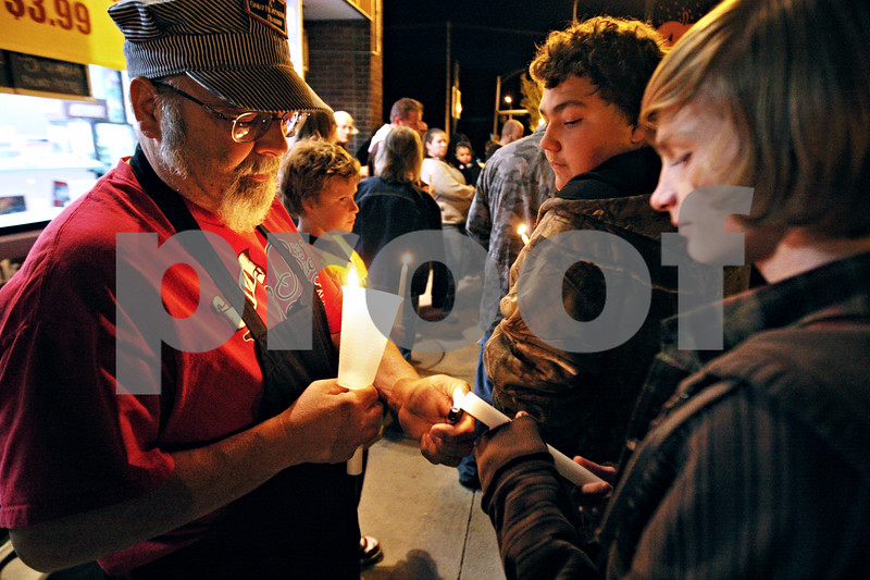 Rob Winner – rwinner@daily-chronicle.com<br /> <br /> On Wednesday night in downtown Sycamore, Frank Riccardi lights a candle for Rocky Quarto, 15, during a candlelight vigil for Riccardi's son, Frank Riccardi Jr.<br /> <br /> 10/07/2009