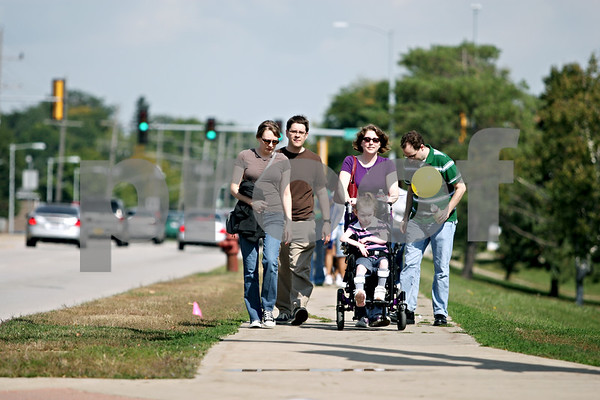 Rob Winner –  rwinner@daily-chronicle.com<br /> (From left to right) Sarah McHone-Chase and her husband David walk alongside friends Lynne and Michael Thomas as they take turns pushing their daughter Caitlin Thomas, 6, as they participate in RAMP's annual Wheel-A-Thon on Saturday in DeKalb.<br /> 09/19/2009