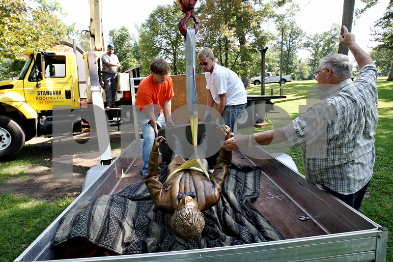 Rob Winner – rwinner@daily-chronicle.com<br /> On Wednesday morning near the bandshell in Hopkins Park, crane operator Ryan Schroeder (from left) begins lifting the new Dee Palmer sculpture with Ben and Matt Larson, while the sculptor Don Morris helps direct.<br /> 08/12/2009<br /> DeKalb<br /> Don Morris - sculptor, plaid shirt<br /> Don Larson - yellowish shirt, dad of two boys<br /> Matt Larson - white shirt<br /> Ben Larson - orange shirt<br /> Ryan Schroeder - crane operator<br /> Herb Buhr - red shirt
