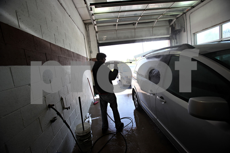 Beck Diefenbach  -  bdiefenbach@daily-chronicle.com<br /> <br /> Jordan Johnston, 18, of DeKalb, power washes a car as it comes through the assembly line at Ralph's Car Wash in Sycamore, Ill., on Saturday May 16, 2009. Johnston is a senior at DeKalb High School and hopes to pick up more hours at the car wash when his summer break begins.