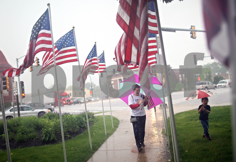 Beck Diefenbach  -  bdiefenbach@daily-chronicle.com<br /> <br /> Julianna Ladas, of Sycamore, and her son Brennan walks amongst the American flags during the rain as they wait for the return of the Sycamore National Guard Unit outside the DeKalb Courthouse in Sycamore, Ill., on Monday June 1, 2009.