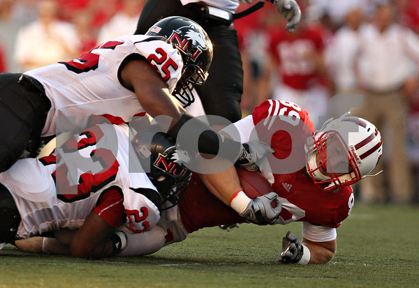 Beck Diefenbach – bdiefenbach@daily-chronicle.com<br /> <br /> Northern Illinois' Kiaree Daniels (23) and Tracy Wilson (25) take down Wisconsin's Shelby Harris (89) during the first half of the game in Madison, Wisc., on Saturday Sept. 5, 2009. Wisconsin beat Northern Illinois 28 to 20.